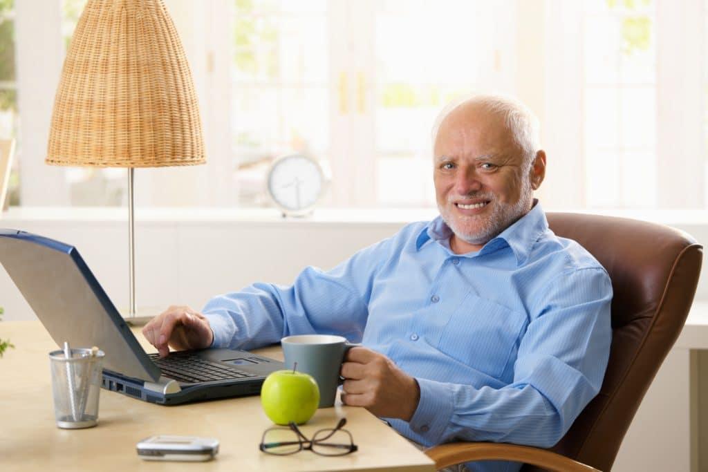 Portrait of happy senior man with computer